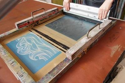 Et billede skæres i et ark papir eller i plast for dermed at skabe en stencil
