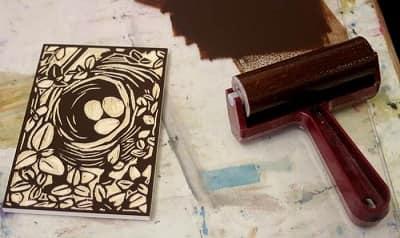 Et billede skitseres på en blok af træ, før der skæres i overfladen med de forskellige gouging værktøjer.